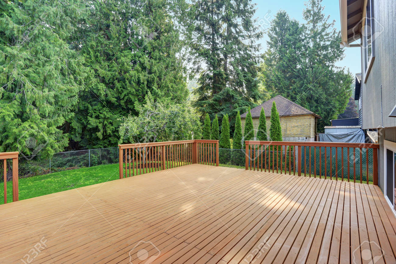 Empty walkout deck boasts redwood railings overlooking well kept back yard. - 86275678