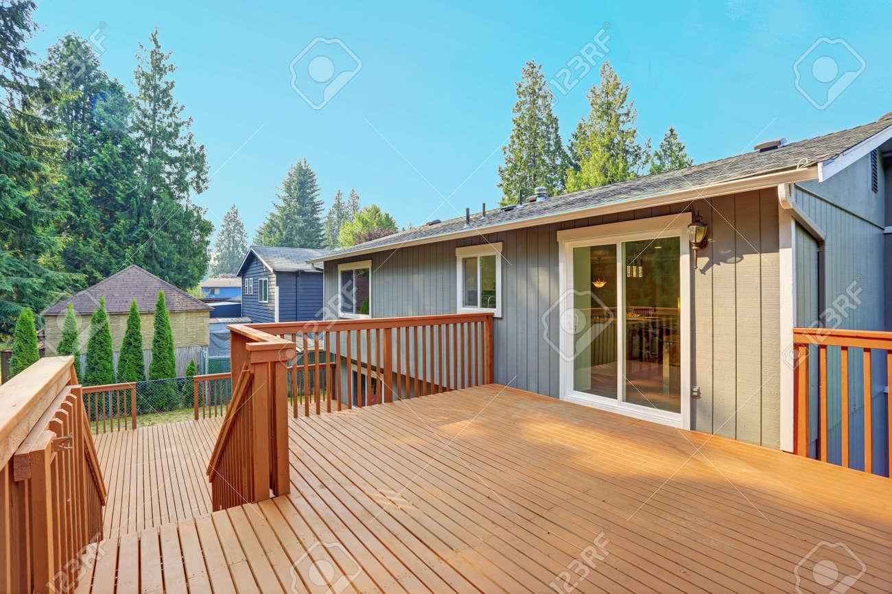 Empty upper level deck boasts redwood railings overlooking the lower level deck. - 86275679