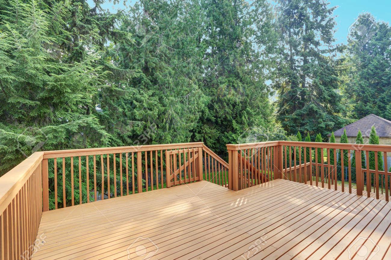 Empty upper level deck boasts redwood railings overlooking the lower level deck. - 86275680