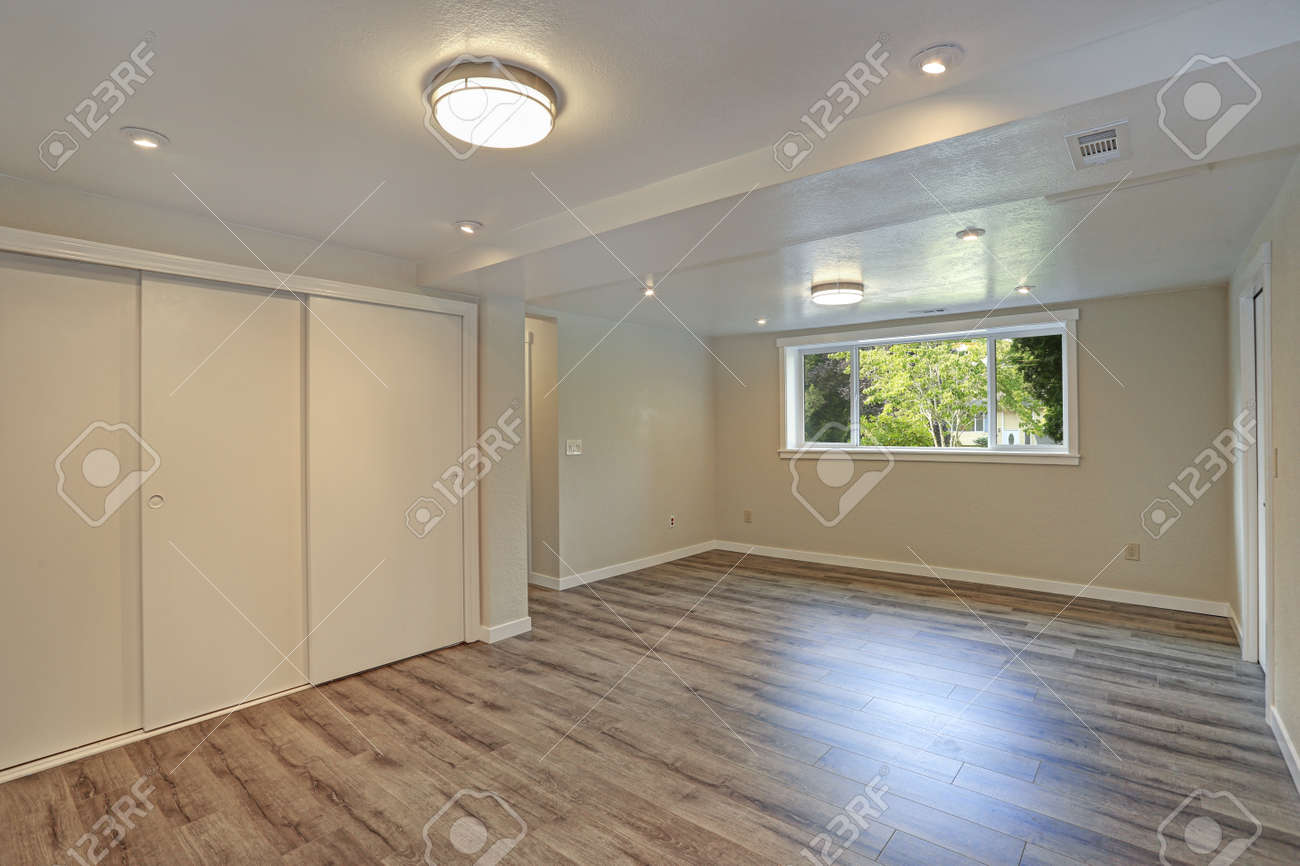 Bright Beige Large Empty Room With Hardwood Floor Built In Closet Small Window