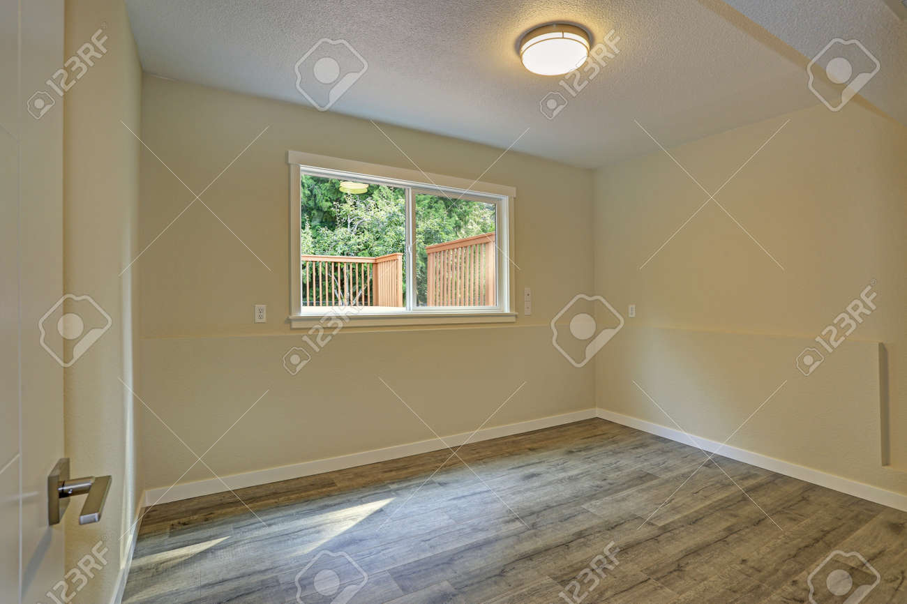 Bright beige large empty room with hardwood floor and a small window american house interior