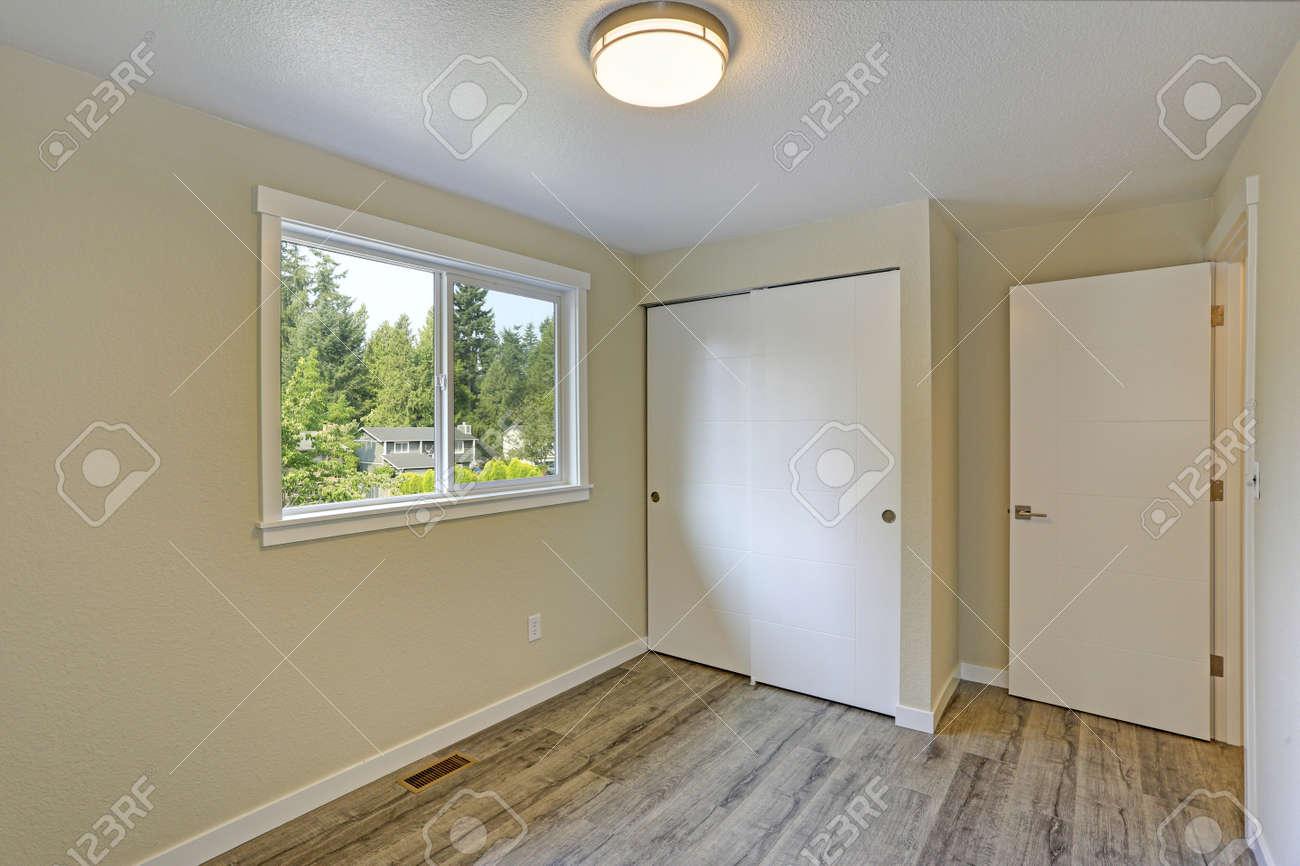 Bright beige empty room with grey hardwood floor built in closet american house
