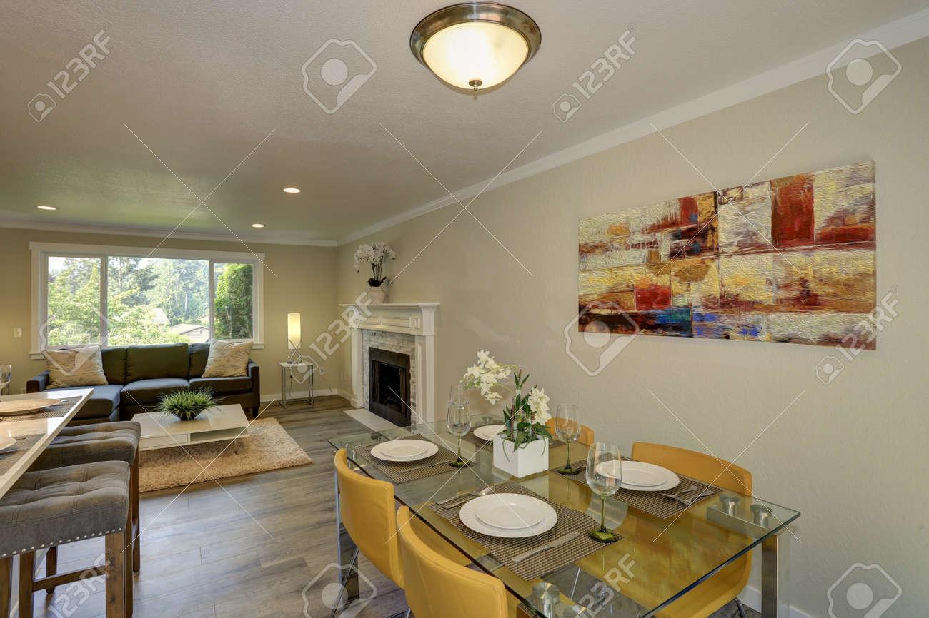 Elegante pequeño diseño de comedor con mesa de comedor de vidrio y sillas  de cuero amarillo frente a la pieza de arte abstracto rojo en la pared.