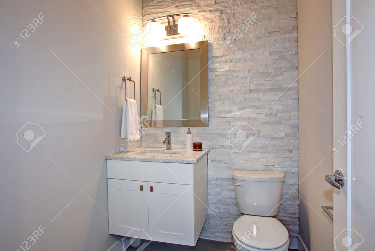 Contemporary White And Gray Bathroom Features Stone Accent Wall Framing A  White Bathroom Vanity Under A