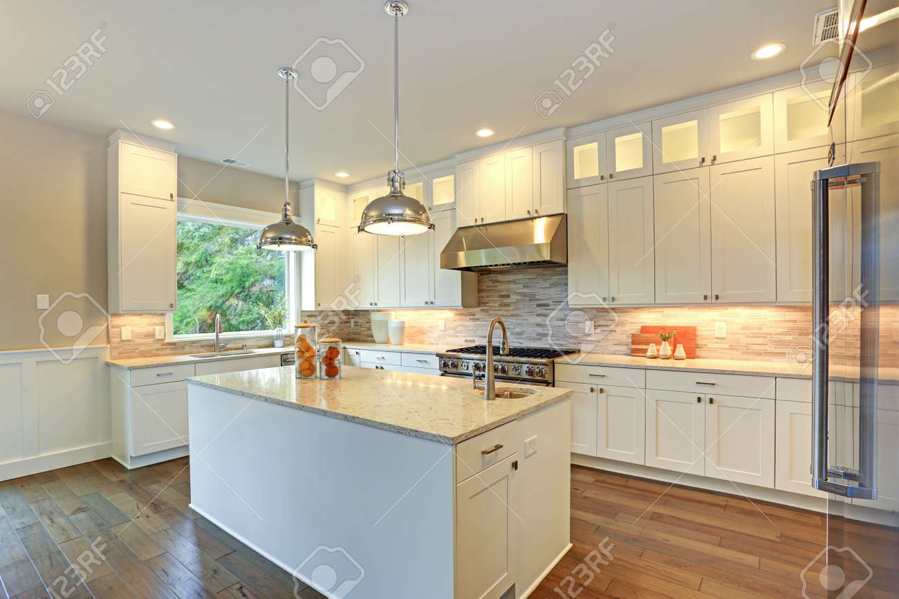 Amazing white kitchen design with white shaker cabinets paired with white and gray marble counters, large White kitchen peninsula and high-end stainless steel appliances. - 88790479