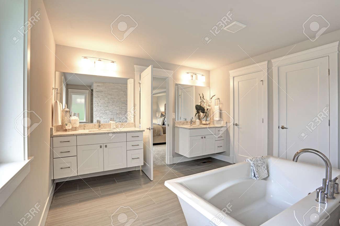 Incredibile bagno padronale con vanità del bagno bianco ripiani