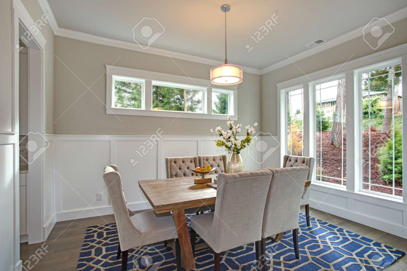 Elegant transitional dining room with board and batten walls,..