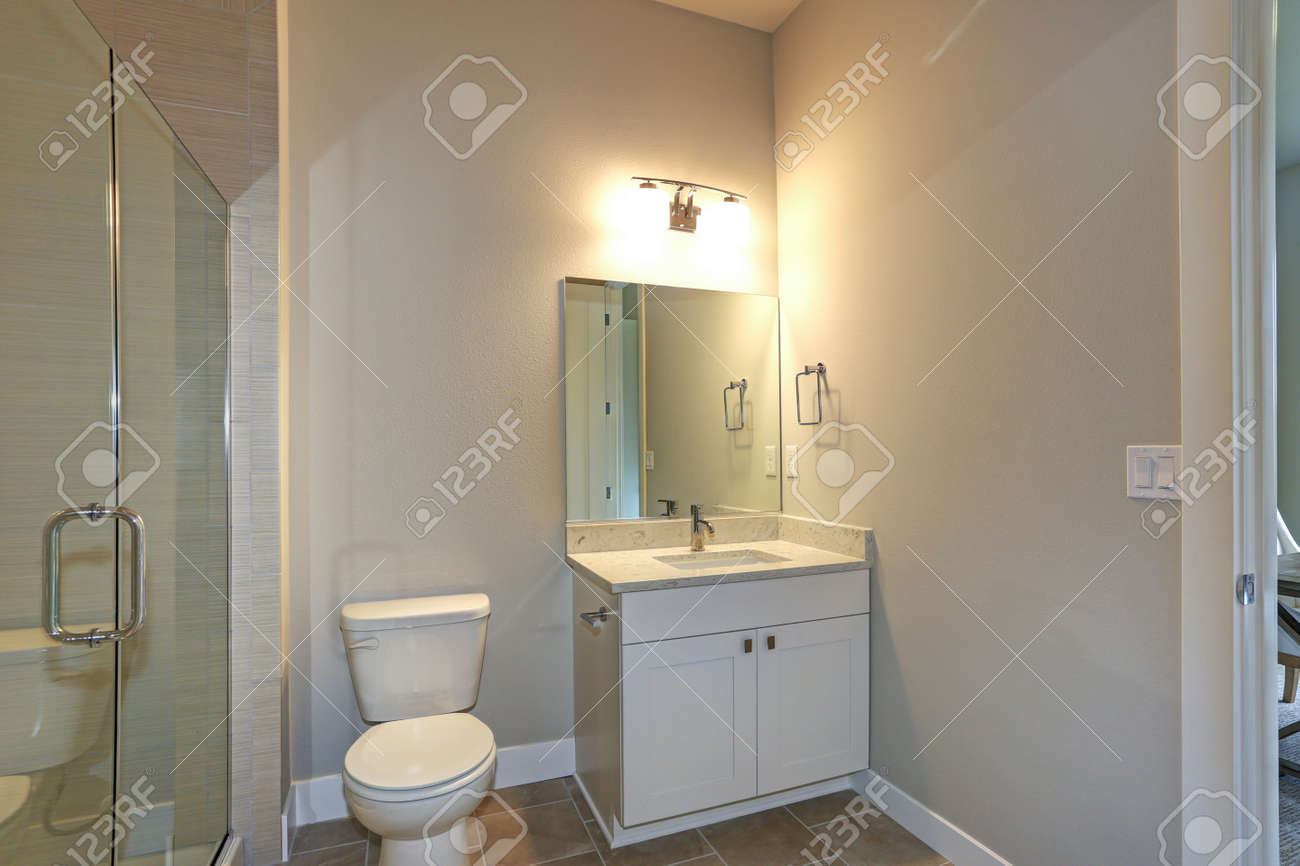 Contemporary White And Beige Bathroom With A White Bathroom Vanity