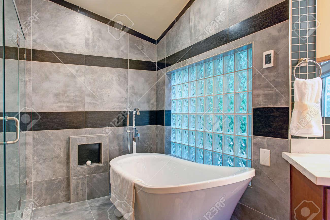 Salle De Bain Carrelage Marbre superbe salle de bain dispose d'une baignoire autoportante blanche bordée  d'un carrelage en marbre gris accentué de rayures carrelées noires et mur  de