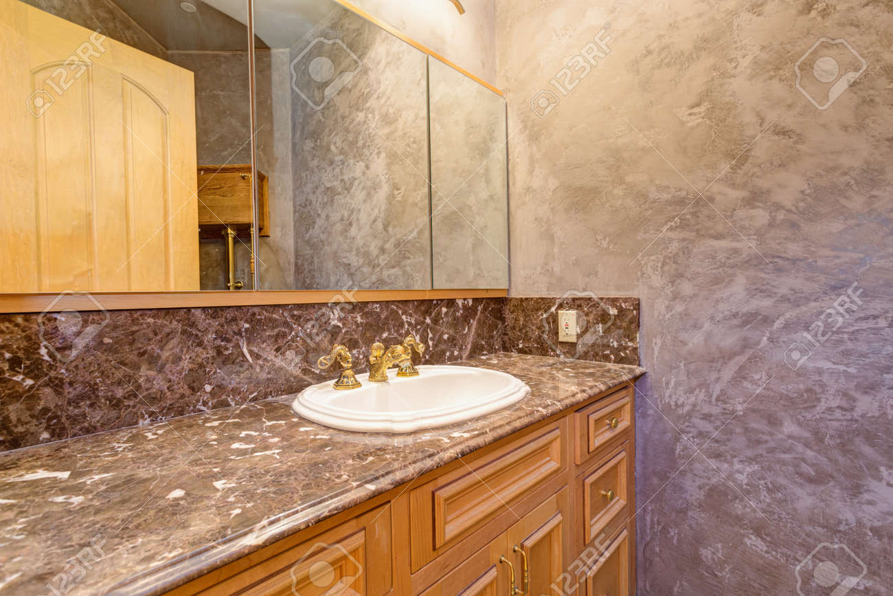 Luxury Mansion Interior Features New Bathroom With Brown Stucco Walls,  Bathroom Vanity Topped With Black
