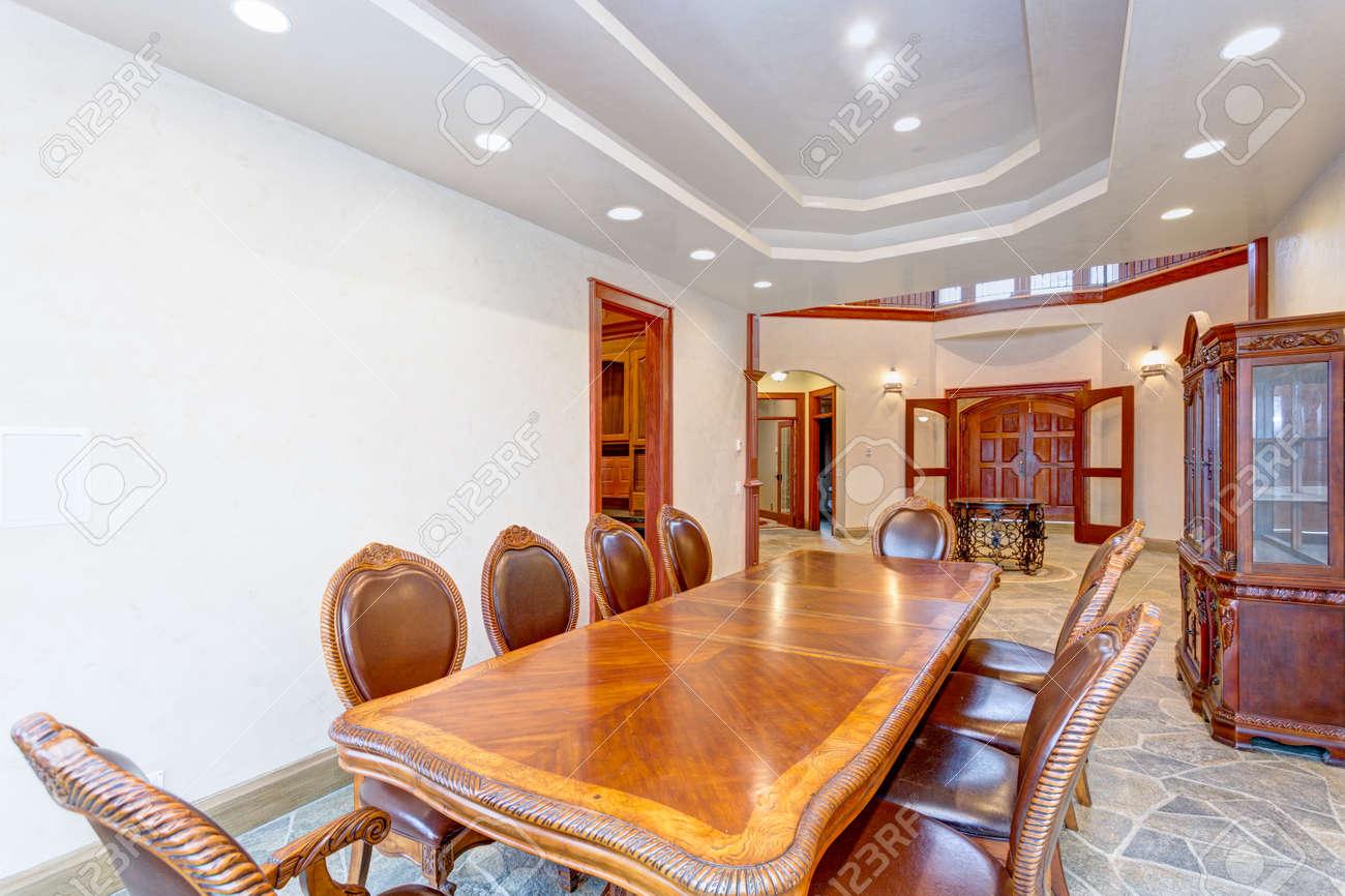 Lujosa y lujosa mansión de comedor cuenta con una mesa de comedor antigua  forrada con sillas de comedor de cuero y un buffet de madera tallada sobre  ...