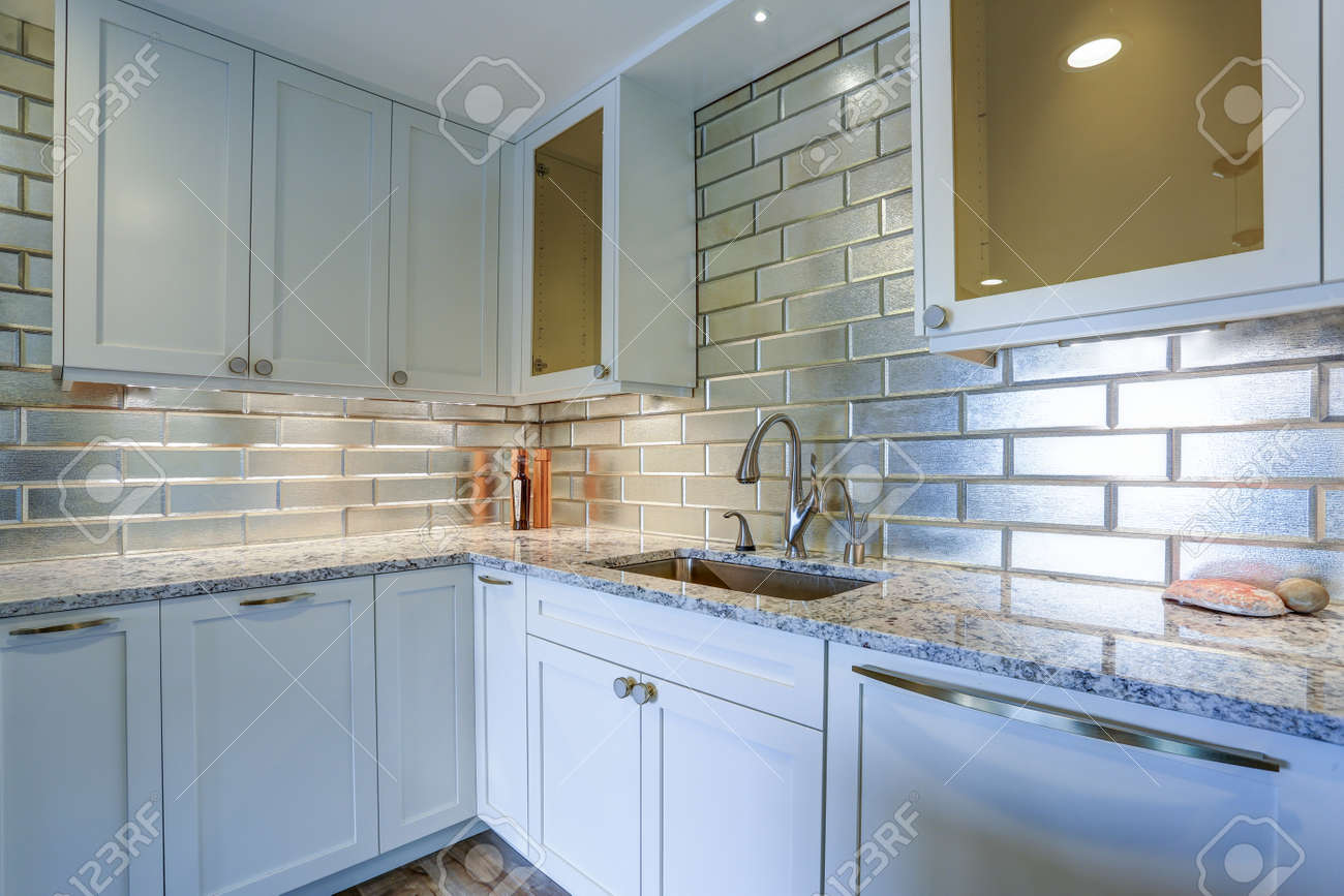 Modern white kitchen design with silver backsplash, white shaker..