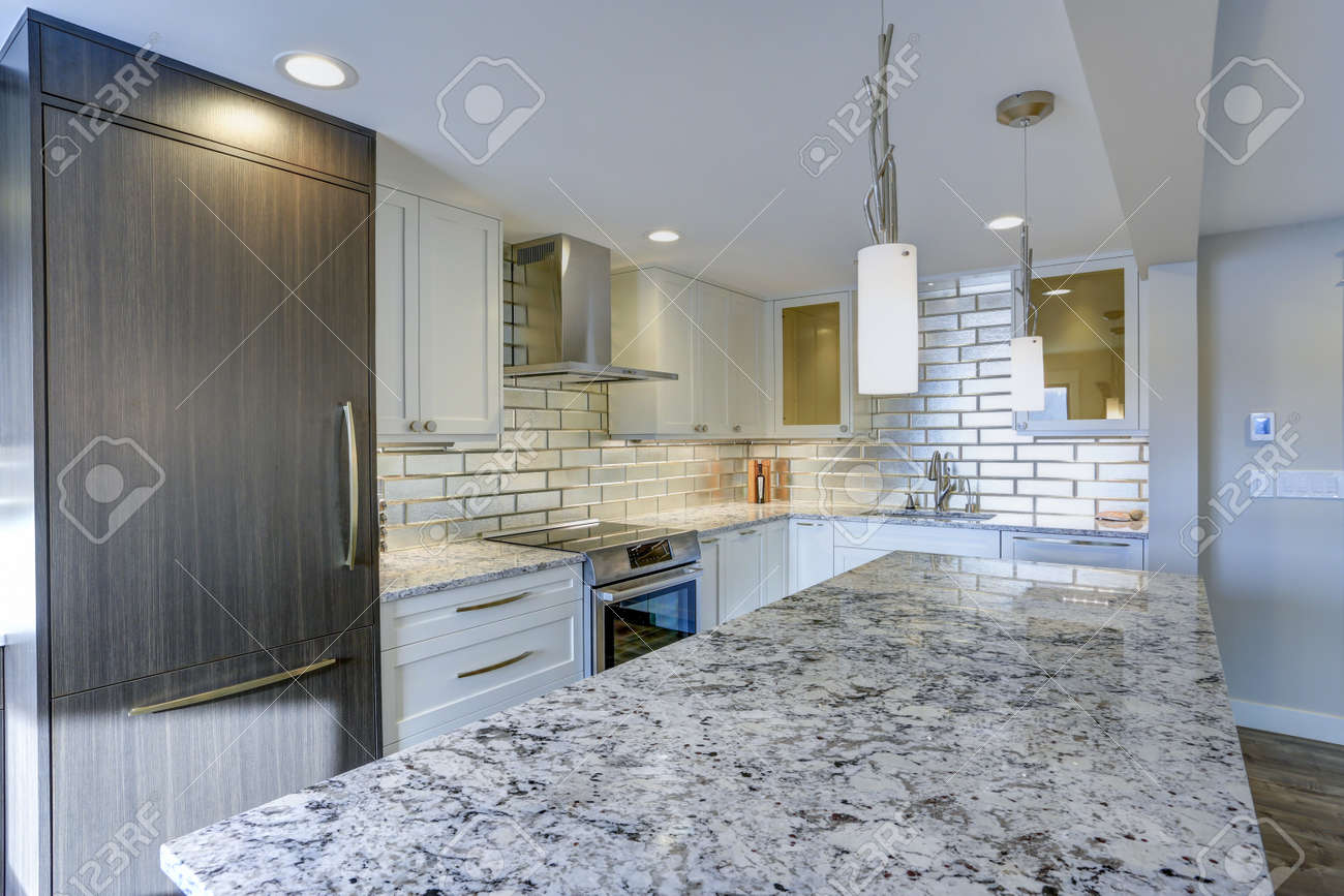 Well appointed kitchen features a large kitchen island topped..