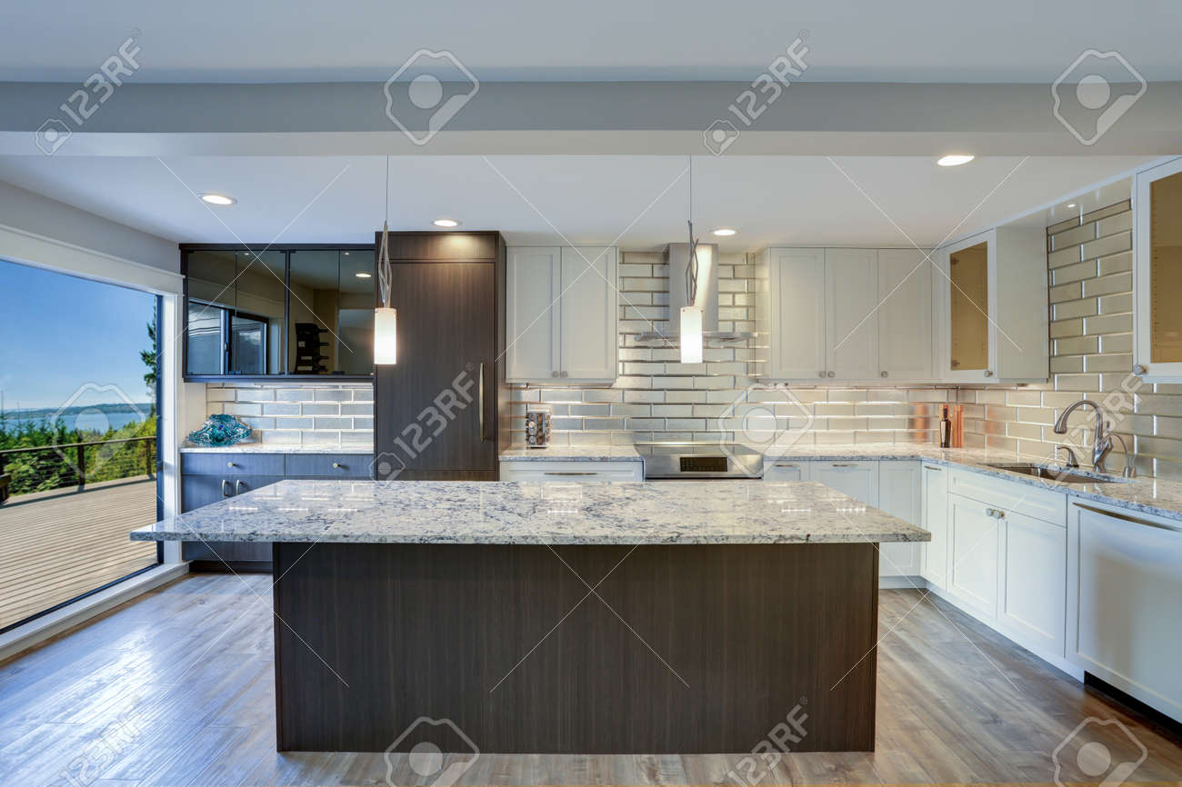 Well appointed kitchen features a large kitchen island, gray..