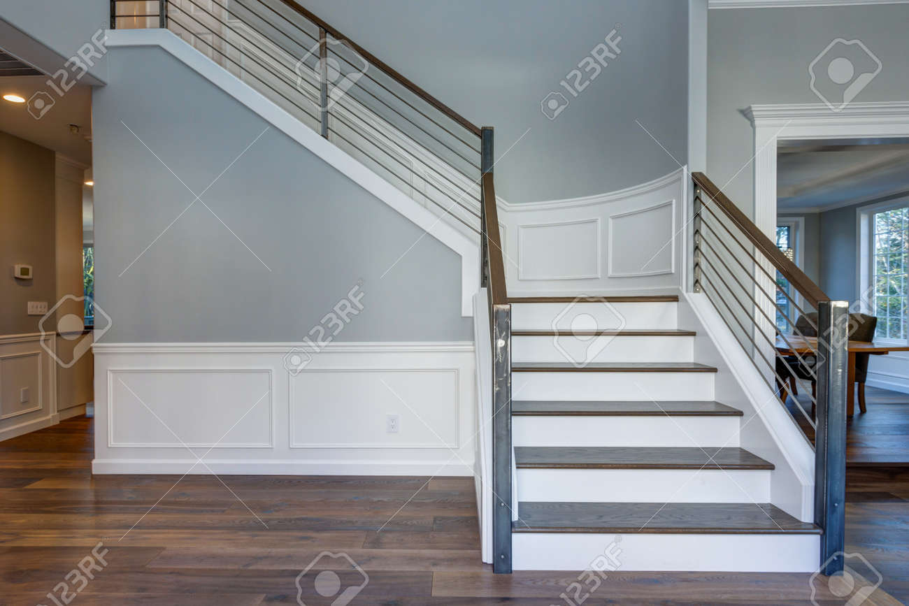 Luxury custom built home interior. Stunning two story entrance foyer design with white wainscoting, grey walls and a white staircase. - 93408476