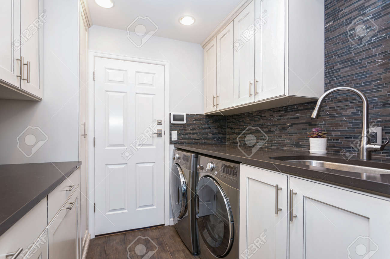 - White Laundry Room Boasts White Shaker Cabinets, Brown Grey Glass