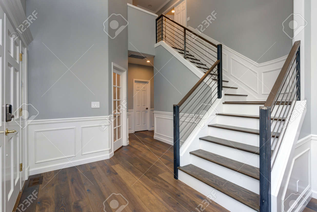 Luxury Custom Built Home Interior. Stunning Two Story Entrance Foyer Design  With White Wainscoting,