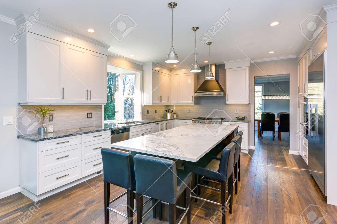Luxury home interior boasts Beautiful black and white kitchen with custom white shaker cabinets, endless marble topped kitchen island with black leather stools over wide planked hardwood floor. - 93392369