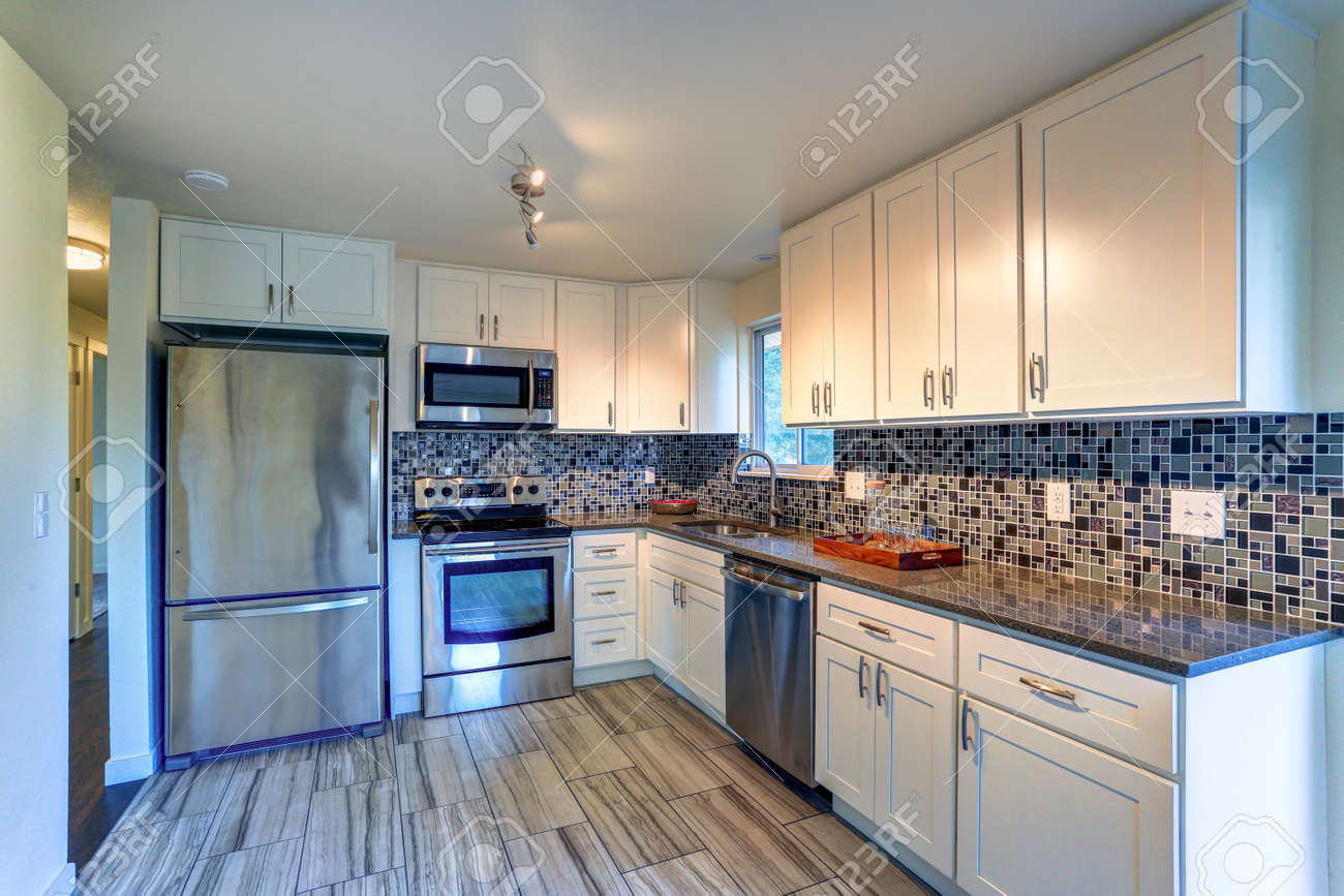 - L-shape Kitchen Room Design With White Cabinets, Brown Granite