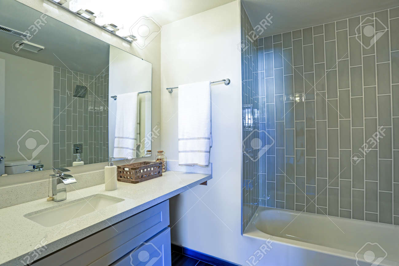 Warm And Clean Bathroom Boasts Grey Glass Tile Shower Surround ...