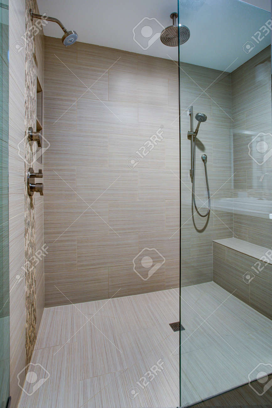 Chic walk in shower with built in bench and beige subway tiled interior accented