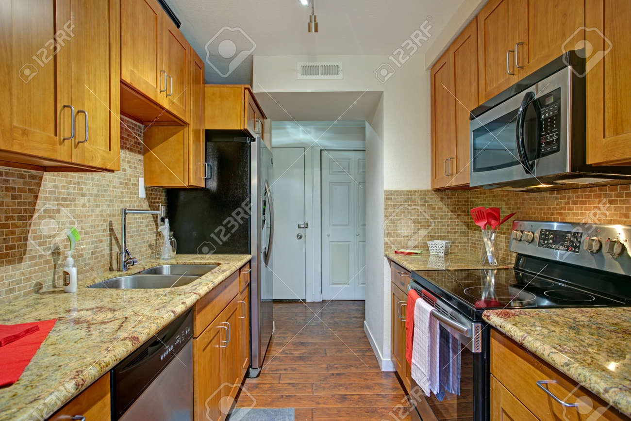 Small Galley Kitchen Design With Black Kitchen Appliances, Maple Cabinets,  Granite Countertops And Backsplash