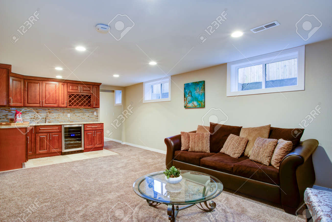 Stunning basement interior boasts a nice wet bar composed of wood shaker cabinets with granite countertop and a mosaic backsplash. - 95664465