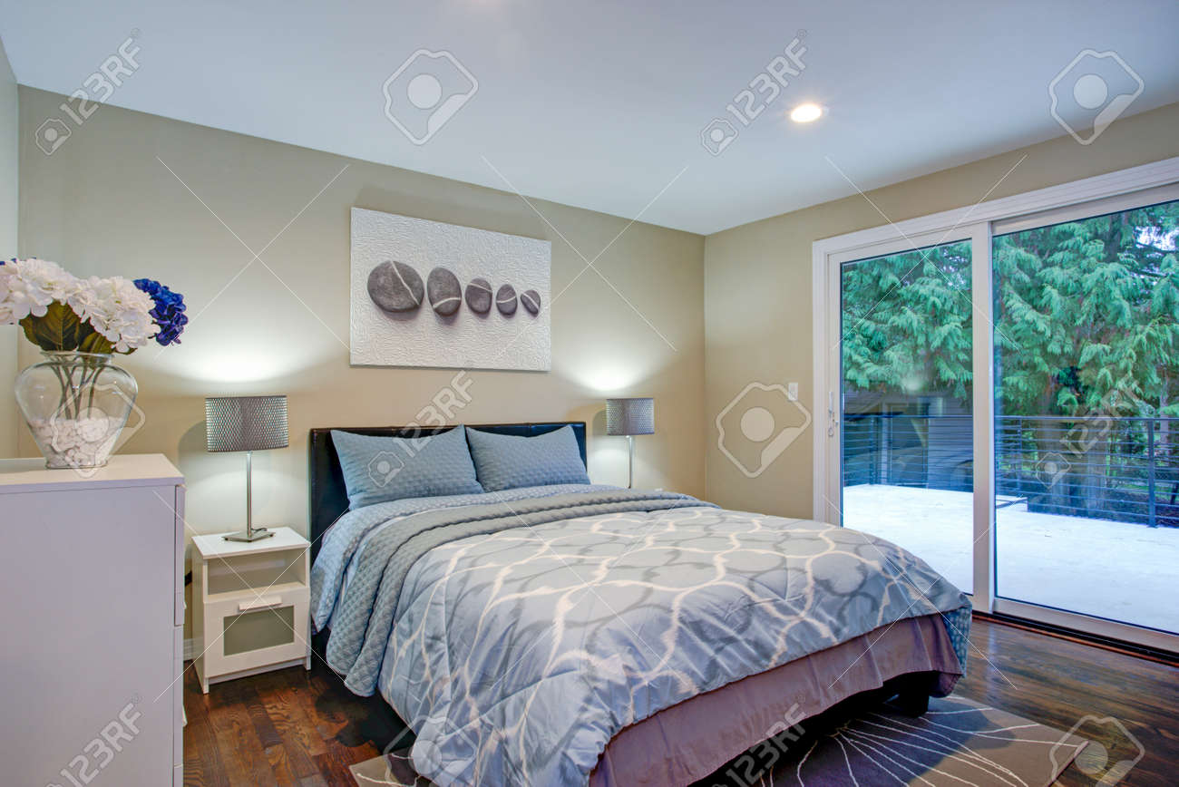 Second floor bedroom with taupe walls, blue bed and private deck.