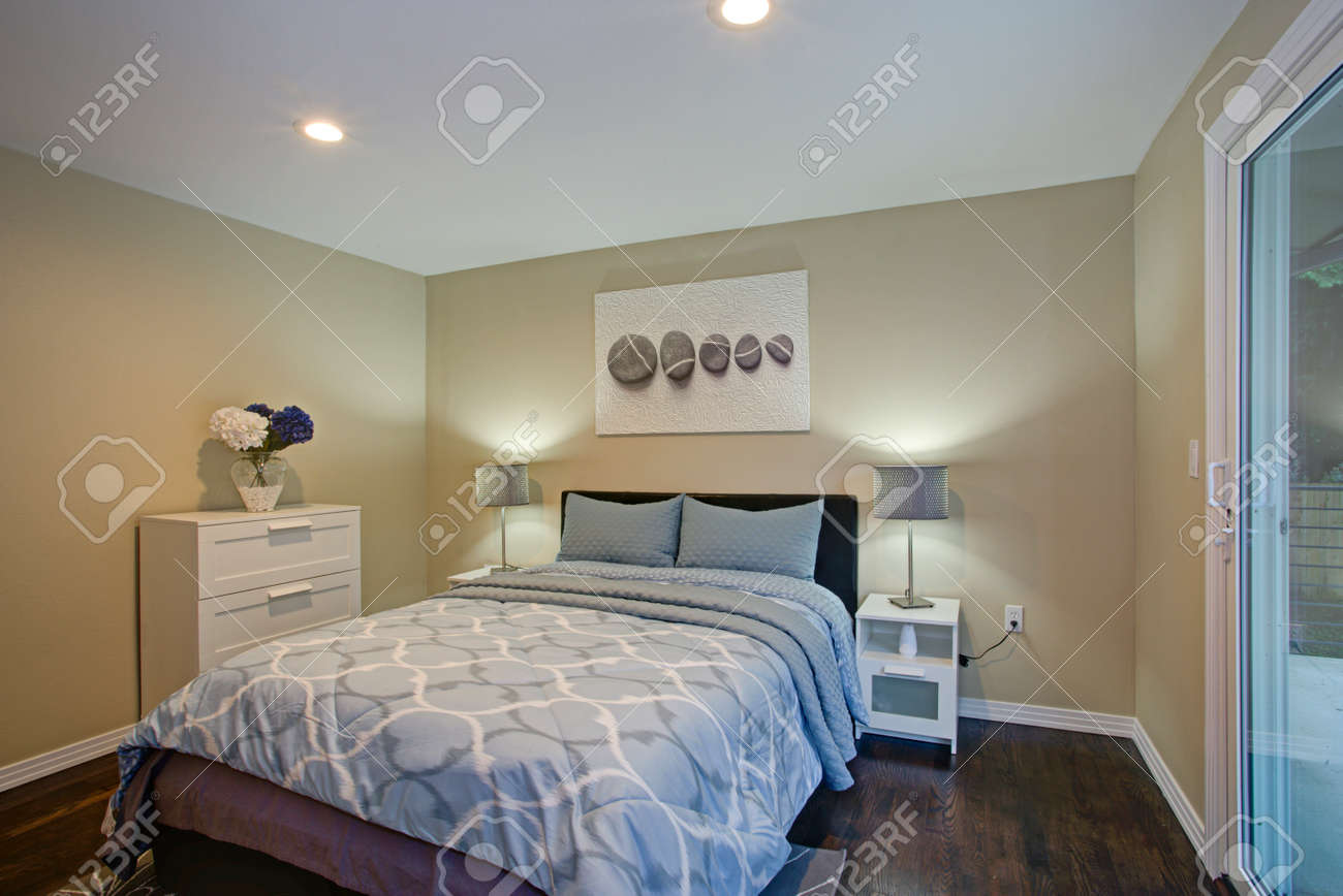 Second floor bedroom with taupe walls, blue bed and private balcony