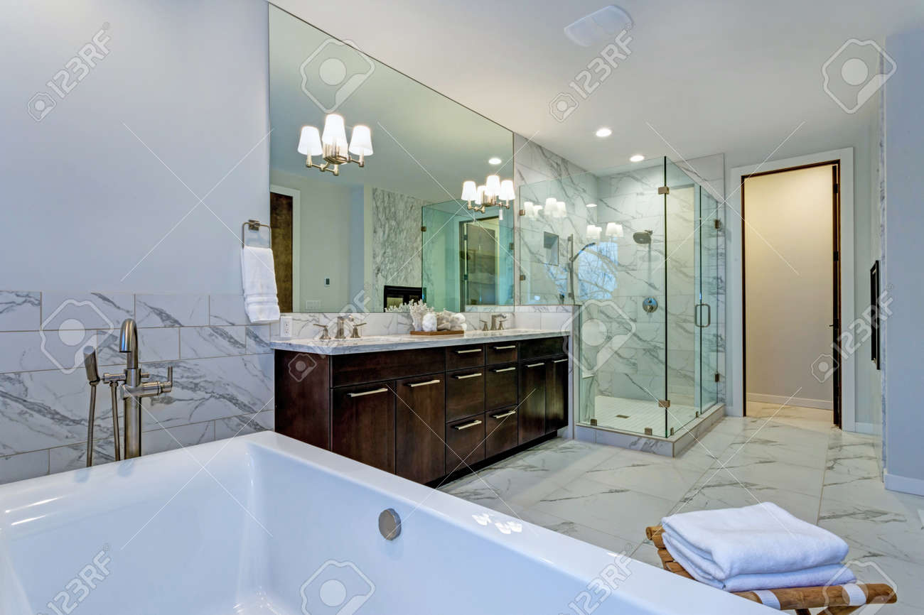 123RF.com & Incredible master bathroom with fireplace Carrara marble tile..