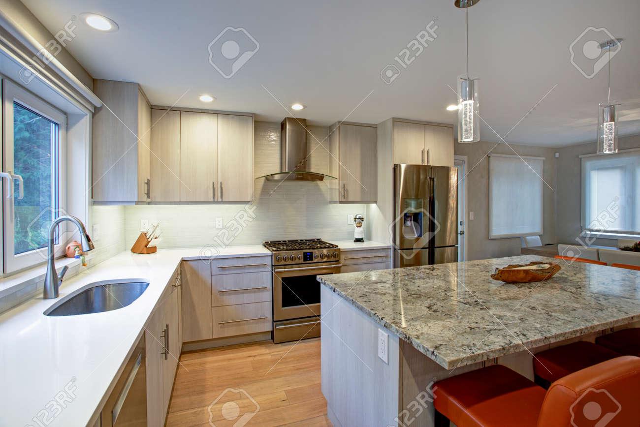 Gorgeous kitchen design features ivory kitchen cabinets flanking..