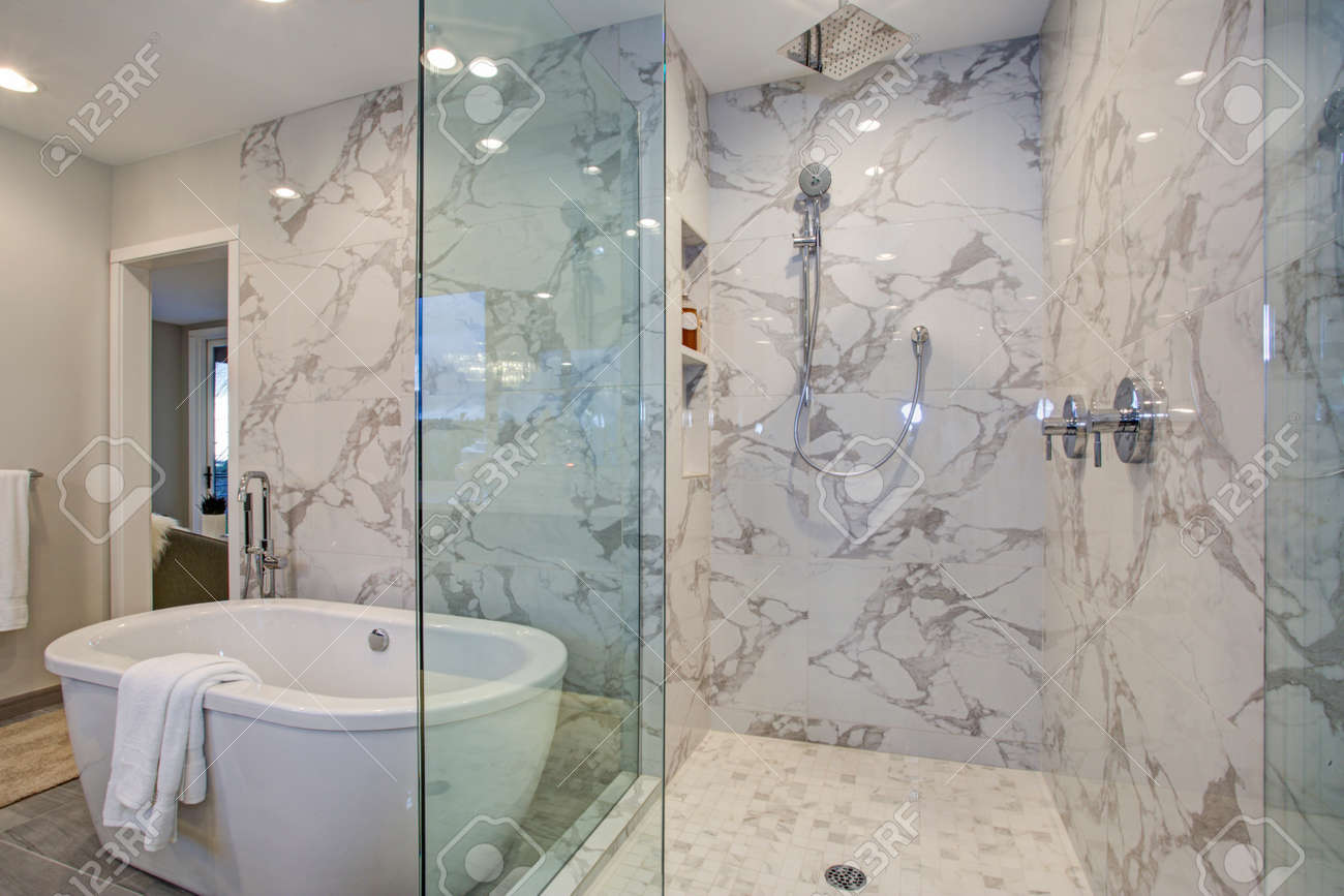 White and gray calcutta marble bathroom design with custom soaking tub and glass walk in shower. - 97873905