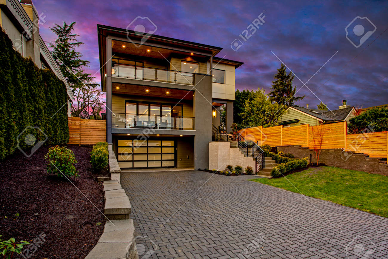 Luxury Modern Home Exterior At Sunset Boasts Four Car Garage With Wide  Driveway. Stock Photo