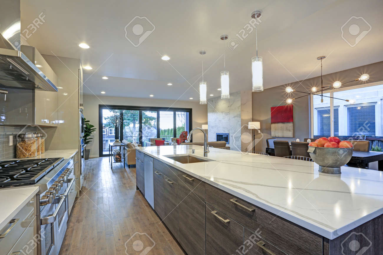 Sleek modern kitchen design with a kitchen peninsula fitted with a gray and white quartz countertop. - 97874016