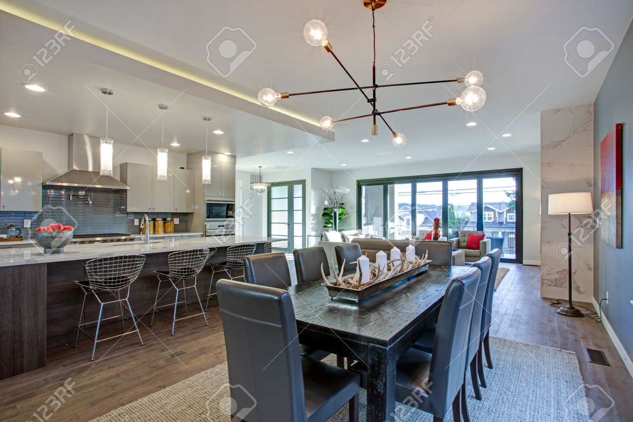 Sleek Modern Kitchen Design With A Large Kitchen Peninsula And Spacious Dining  Area With Black Wood