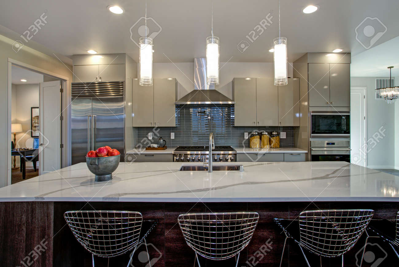Sleek modern kitchen design with a kitchen peninsula fitted with a gray and white quartz countertop
