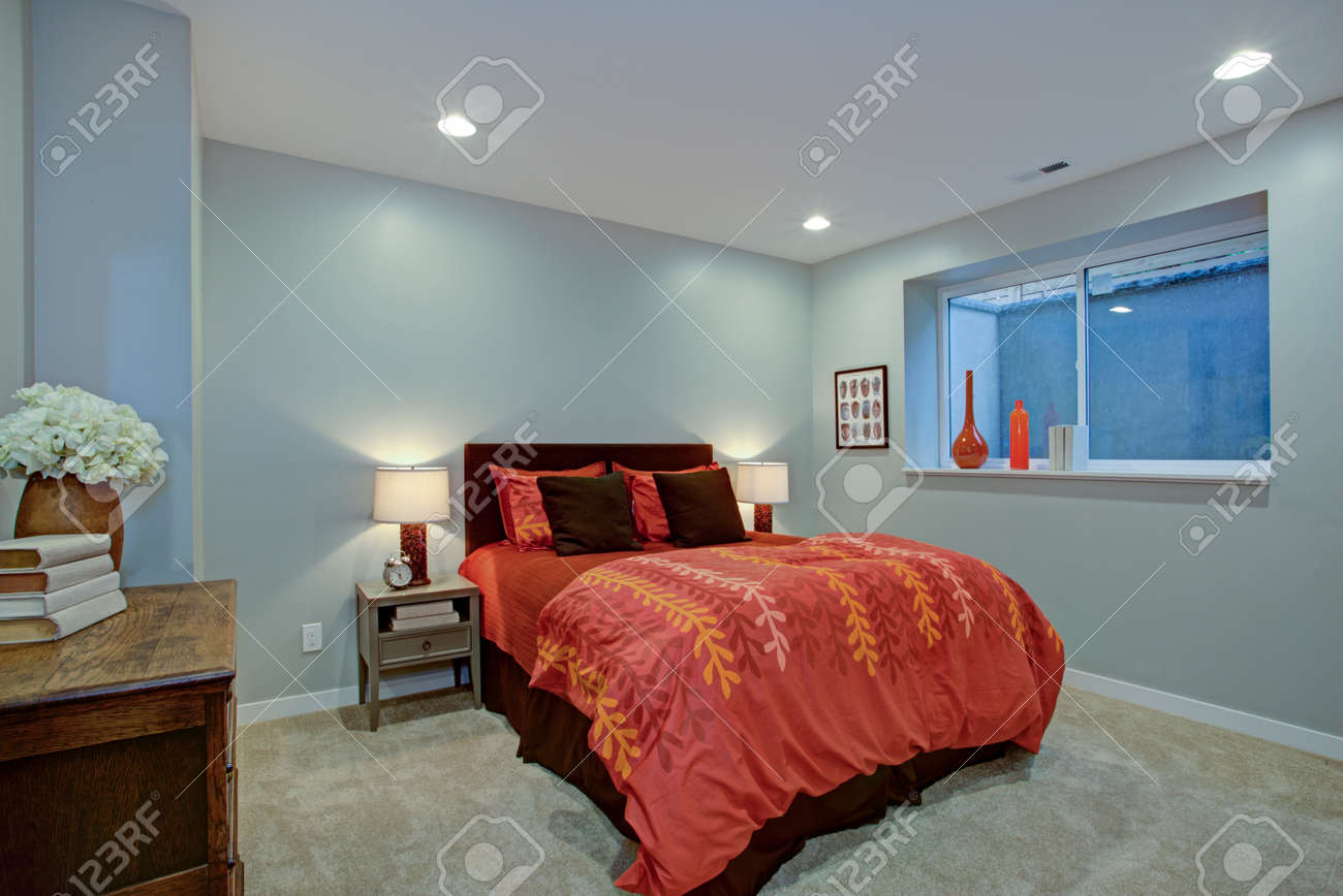 Charming bedroom design with soft blue walls and red bed.