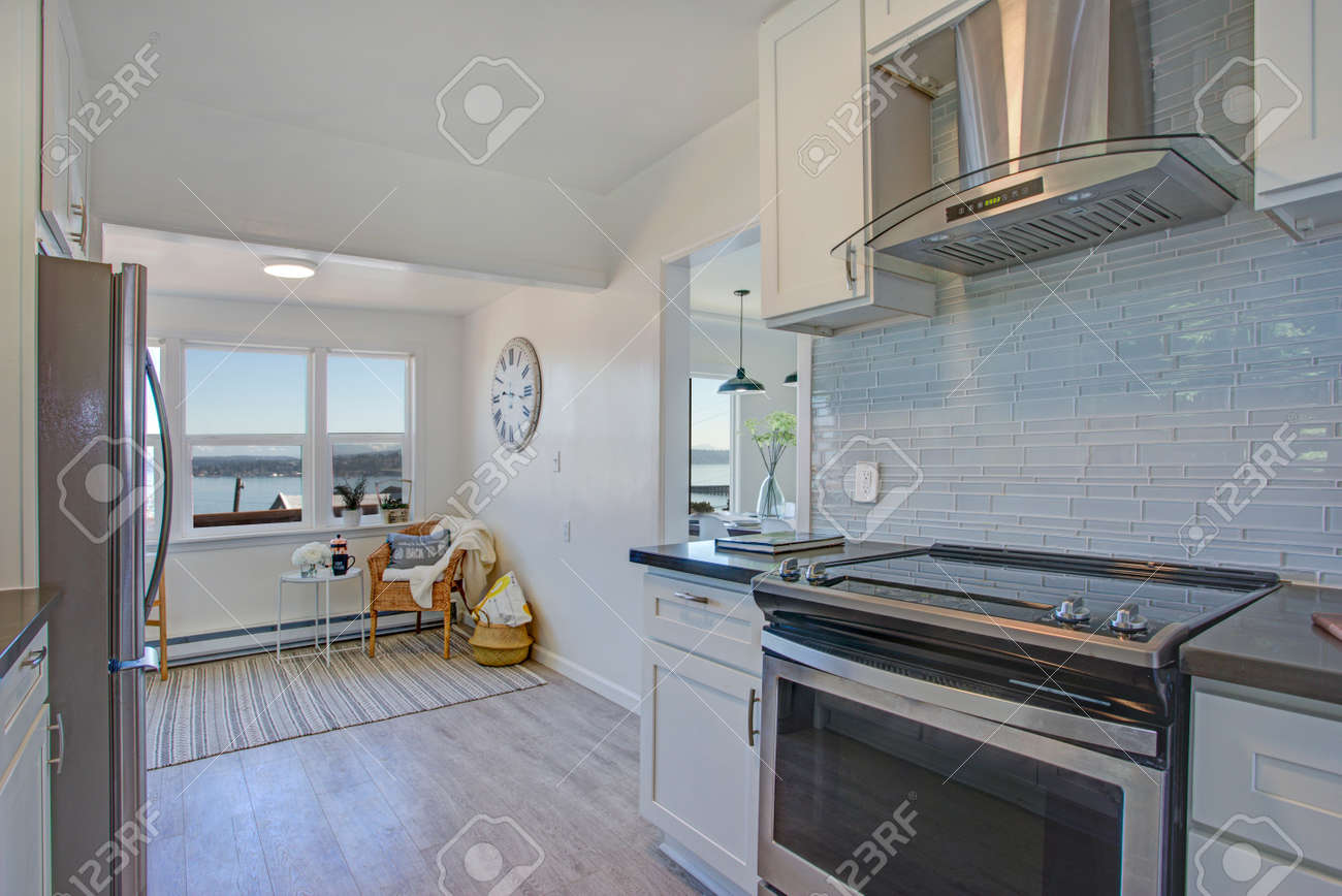 White And Gray Kitchen With Light Filled Sitting Area. Stock Photo ...