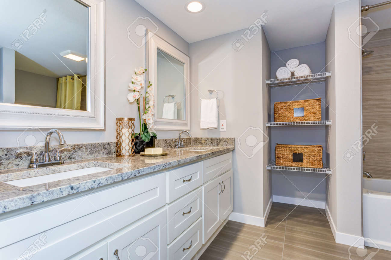 Elegant bathroom with long white vanity cabinet, granite counter top, two sinks and built in shelves. - 99607367