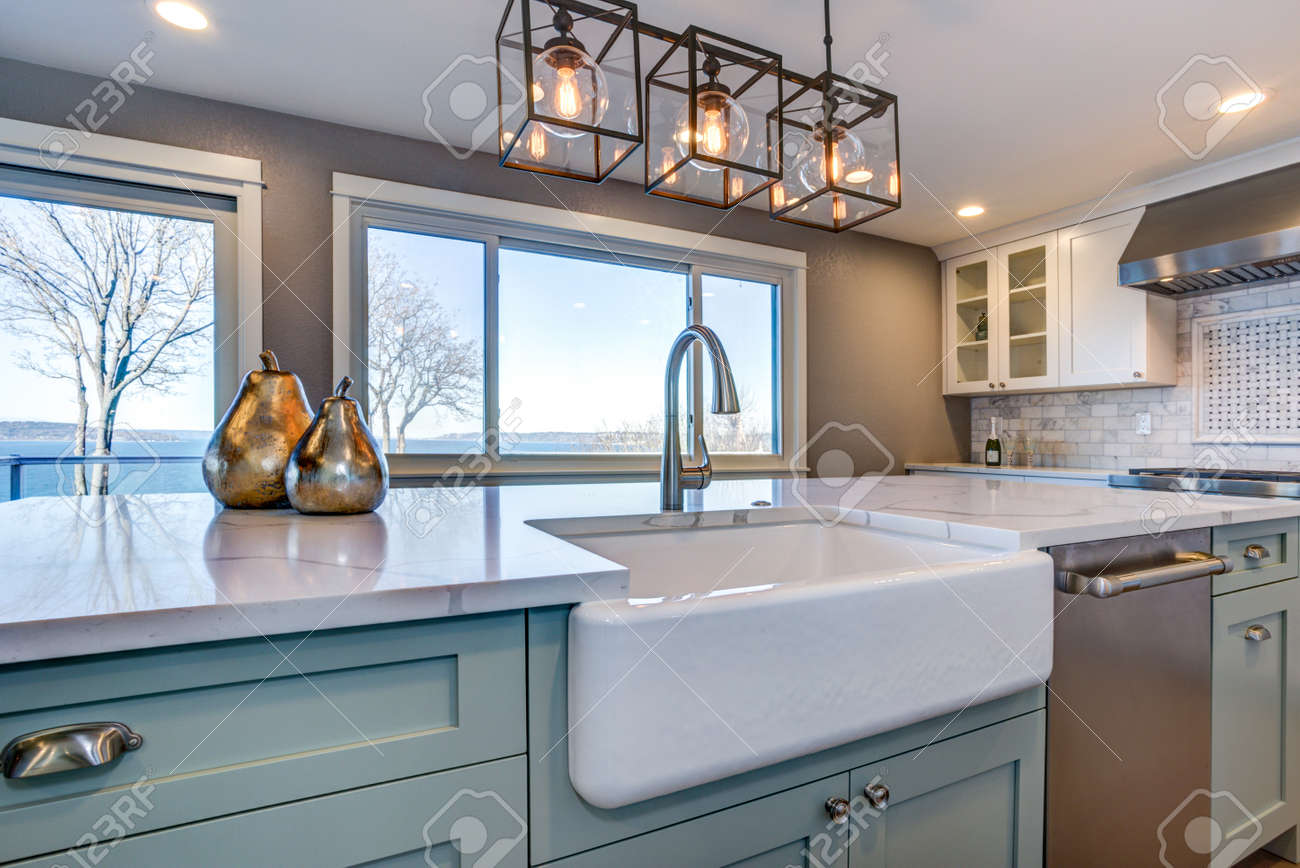 Beautiful kitchen room with green island and farmhouse sink. - 100275846