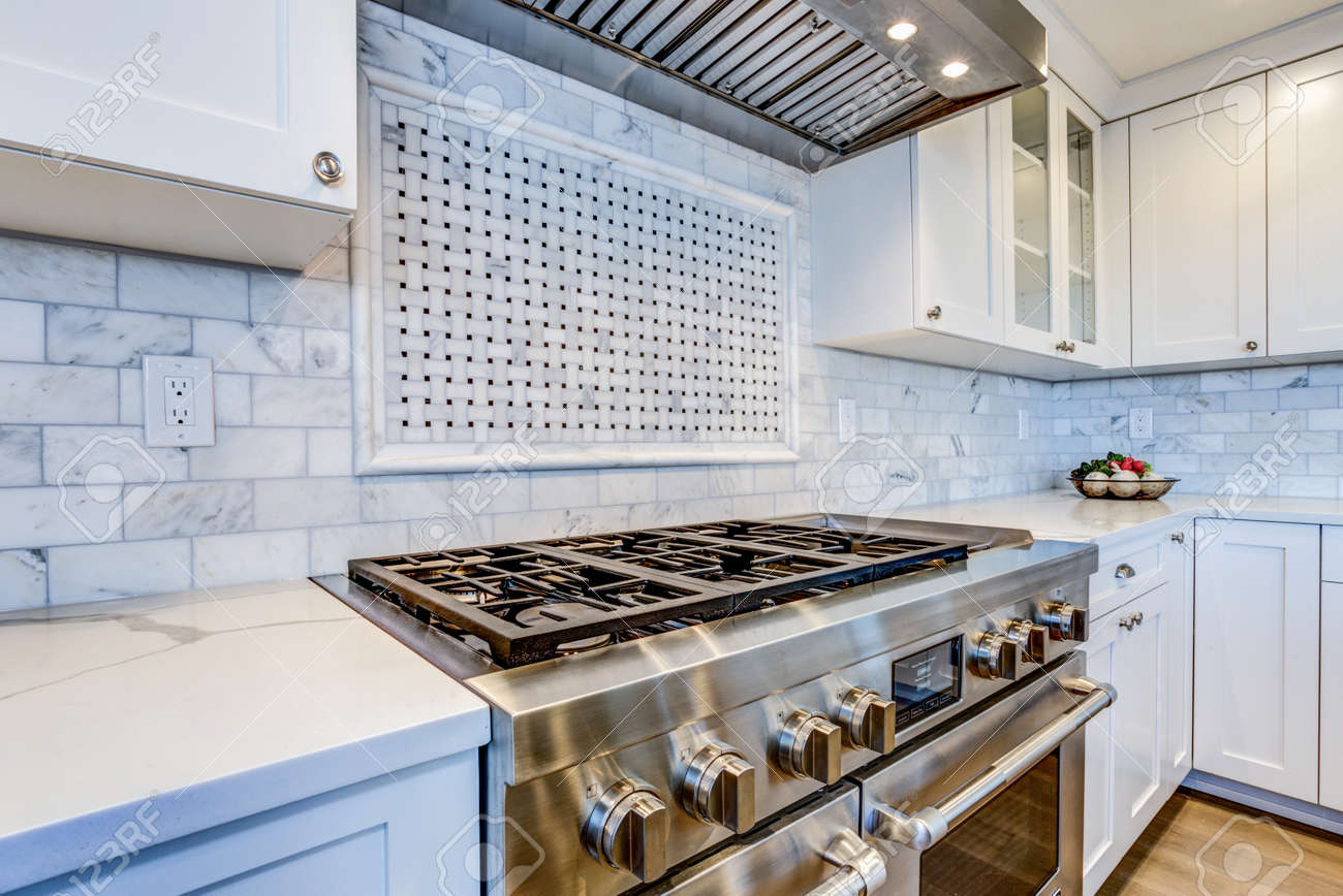 White Kitchen With Stainless Steel Hood Over Gas Cooktop And Stock Photo Picture And Royalty Free Image Image 100252581