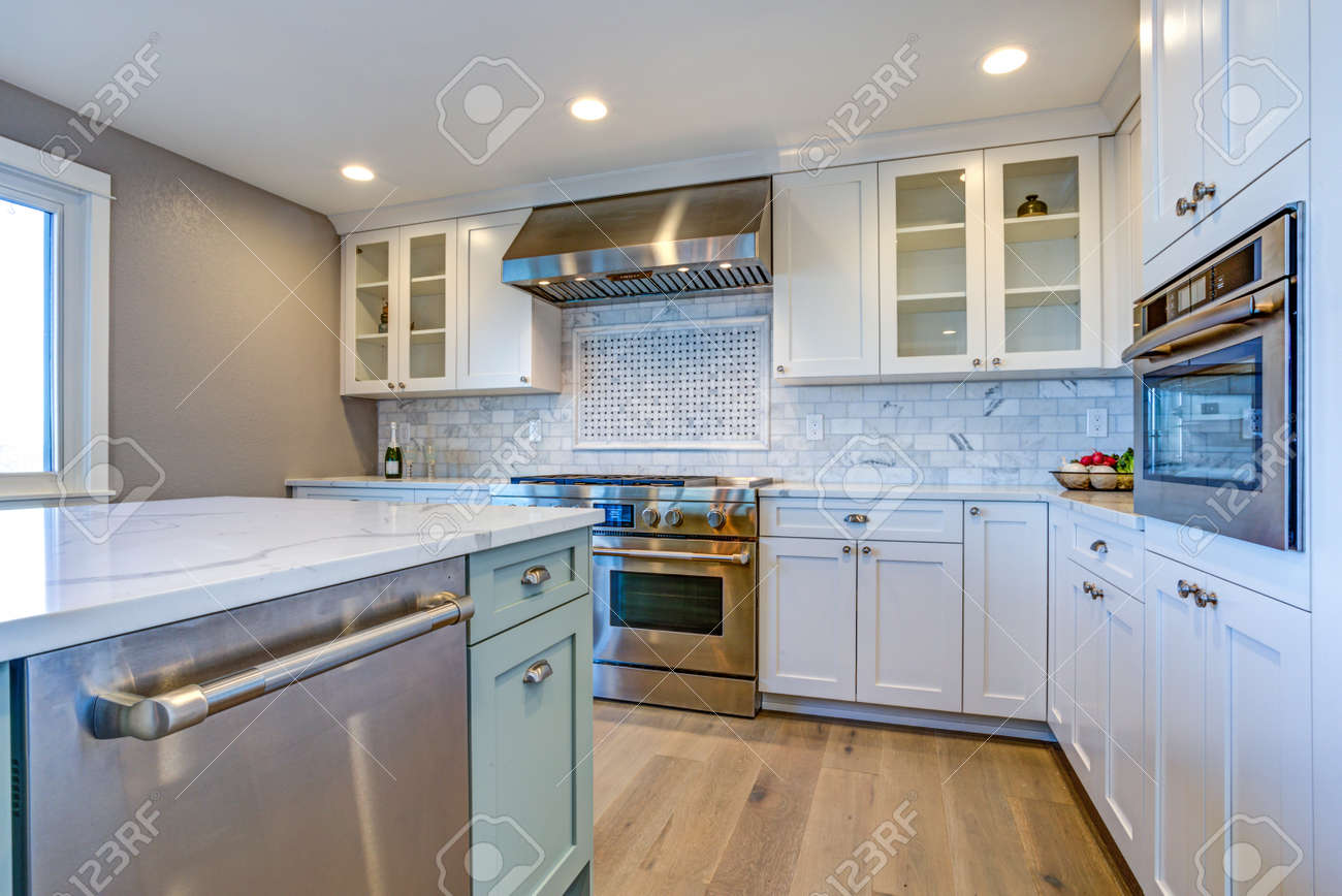 - White Kitchen With Stainless Steel Hood Over Gas Cooktop And