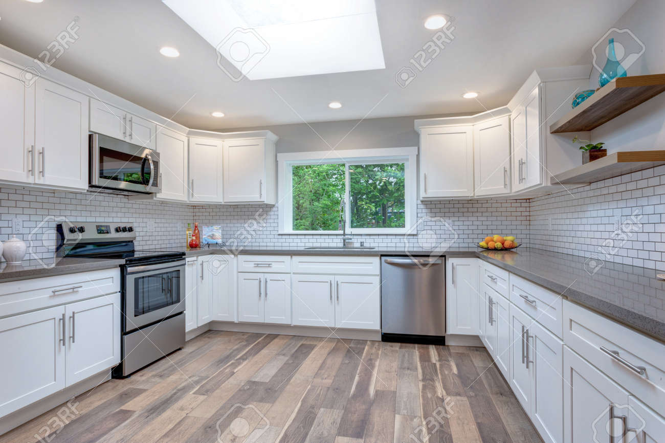 - Open Concept Kitchen With White Cabinets, Grey Quartz Countertops