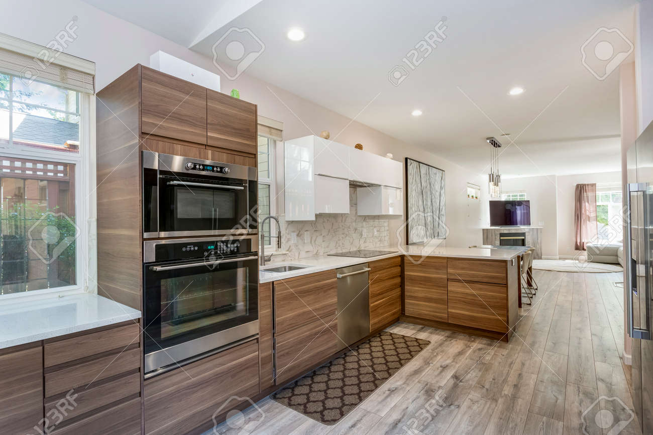 Awesome kitchen room with quartz countertops, new wooden cabinets and modern laminate floor. - 107737530