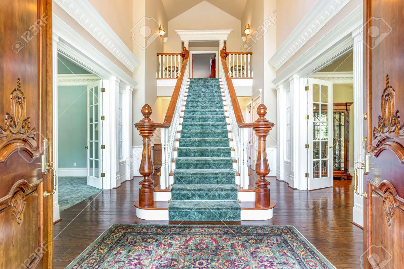 Grand two story foyer with elegant staircase and colorful rug on the floor. - 108106287