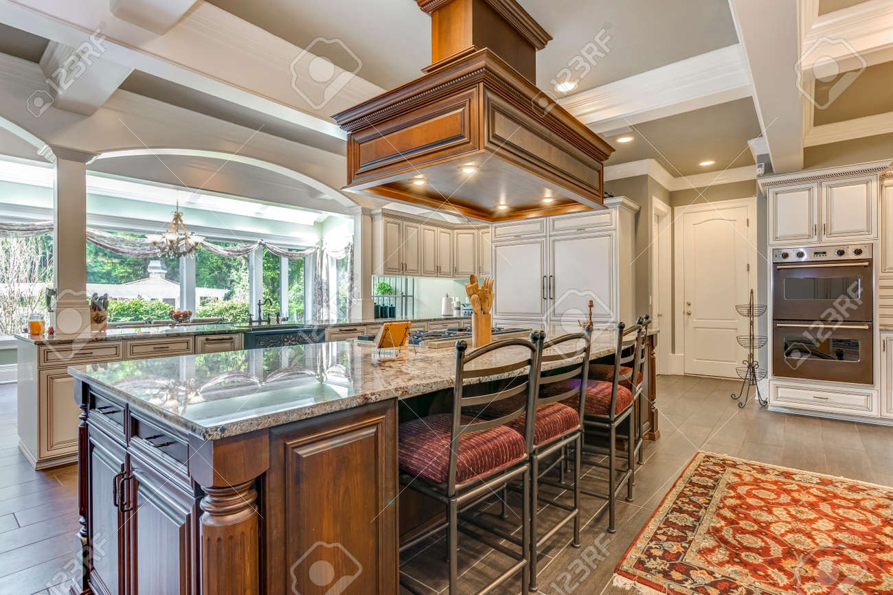 Stunning kitchen room design with large bar style island and coffered ceiling. - 108106293