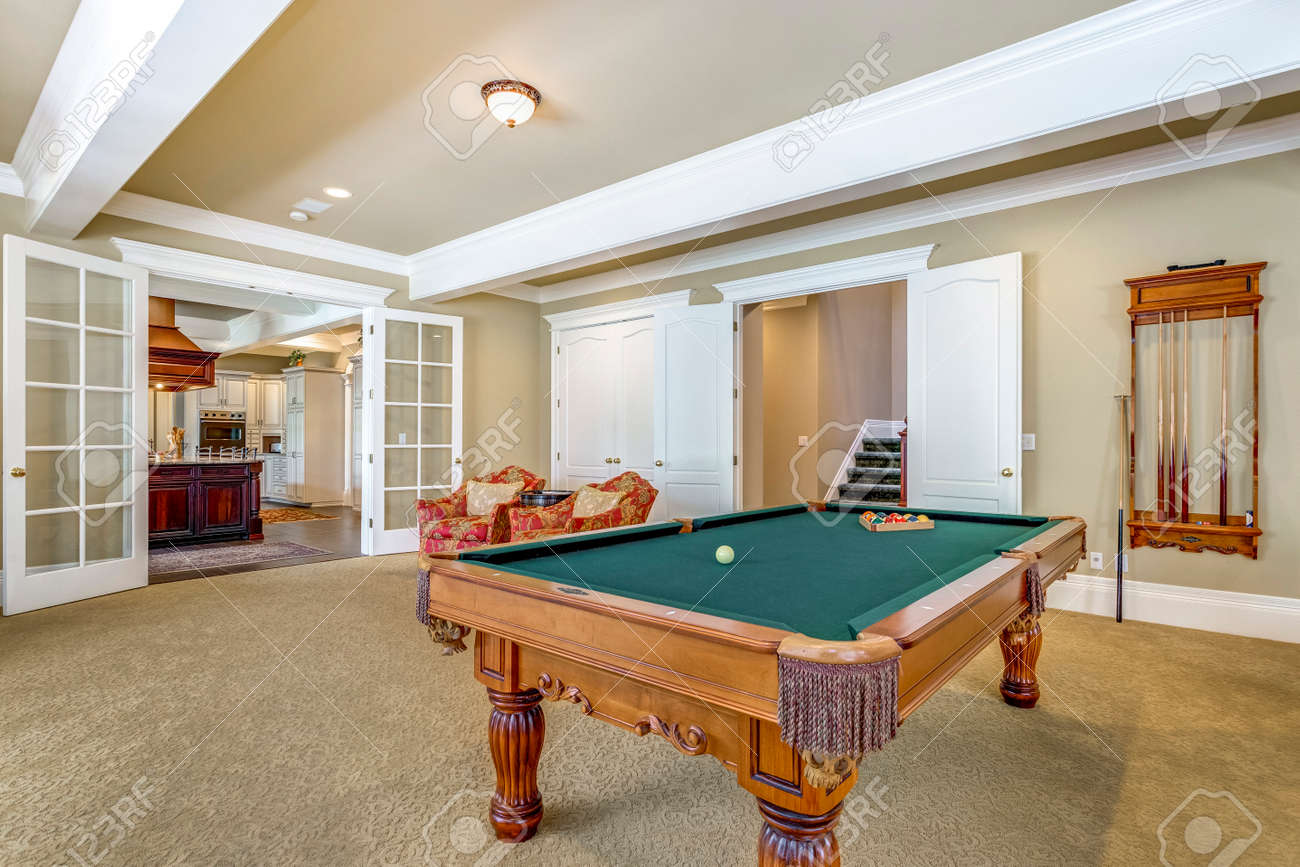 Light brown game room with green billiard table. - 108106296