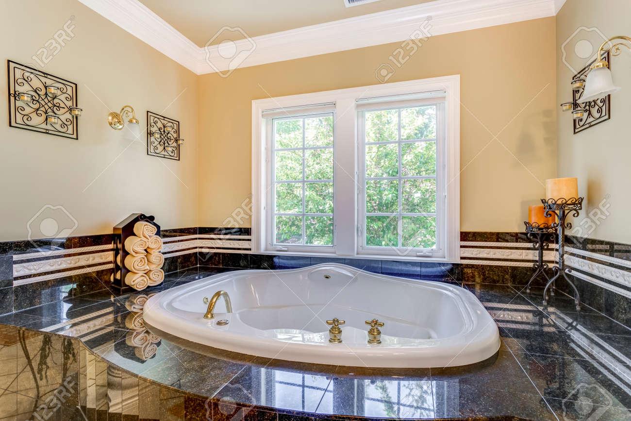 Elegant master bathroom interior boasts tub nook with hot tub and black tile surround. - 108106227