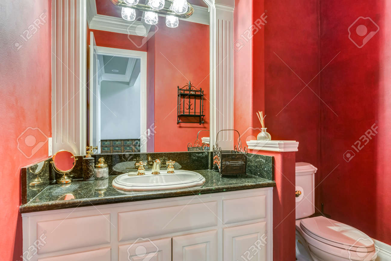 Red bathroom design with white vanity cabinet and marble counter top. - 108106232
