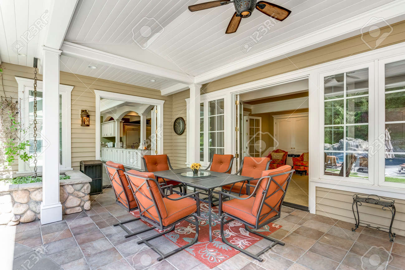 Spacious covered deck area with table and red outdoor chairs under white plank ceiling. - 108106233